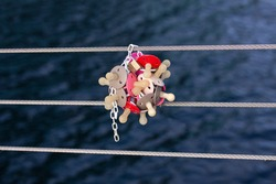Bunch of baby pacifiers and a padlock fixed to a railing wire on a bridge. Hanging the dummies helps the toddler to get rid of them is a tradition in Scandinavia. Close-up image.
