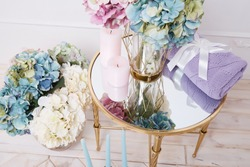 Bunch of beautiful lush fragrant hydrangea flowers stand in transparent glass vase gold plaid blanket knit from wool acrylic silk tied with satin ribbon candle mirror table comfortable interior house.