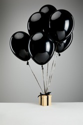 bunch of black balloons with gift box isolated on grey, black Friday concept
