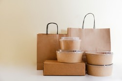 Bunch of blank disposable containers for takeout food stacked with paper bags and boxes with copy space for brand's logo. Close up shot of eco friendly to go carton bowls on table.