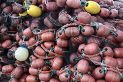 bunch of brown and yellow fishing net floats of piled up fishing nets