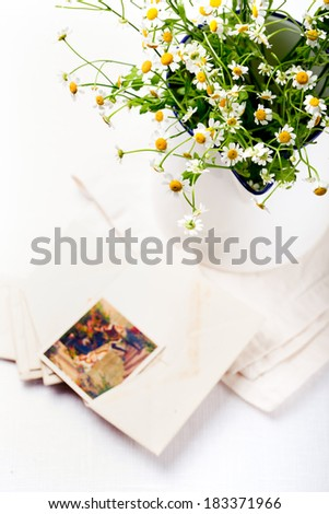 Bunch of chamomile, daisy flowers in an enamel metal vintage jug with a vintage postcards and envelopes on a white textile background