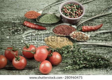 Bunch of cherry tomatoes, herbs, small bowl and antic metal spoons with different kinds of spices, sea salt and red hot chili peppers on old wooden board. Selective focus. Toned.