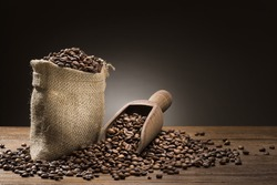 bunch of coffee beans with burlap sack and wooden scoop on table.