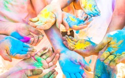 Bunch of colorful hands of friends group having fun at beach party on holi color festival summer vacation - Young people enjoying time together - Youth friendship concept with multicolored powder game