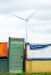 bunch of colorful, rusty metal containers with wind turbine on background.