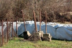 Bunch of completely rusted metal poles with concrete foundation left from destroyed wire fence in family house backyard next to temporary flood protection wall made of box barriers covered with thick