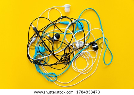 Bunch of different earphones isolated on yellow background. Color conceptual. Conceptual minimalism. Minimal thing. Minimal think. Tangling bunch of earphones wires. Tangled cable Foto stock ©