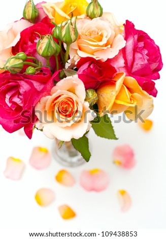bunch of different roses in a glass