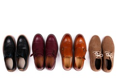 Bunch of different style men's shoes in a row. Close up shot chukka boots, single and double monk strap oxfords, brown, black and burgundy brogues. Top view, copy space, flat lay, white background