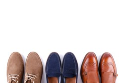 Bunch of different style men's shoes in a row isolated on white background. Chukka boots, penny loafers and double monk strap oxford shoes. Top view, copy space for text, close up, flat lay.