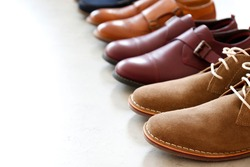 Bunch of different style men's shoes in a row isolated on white background. Close up shot chukka boots, single and double monk strap oxfords, brown and burgundy shoes. Top view, copy space, flat lay.