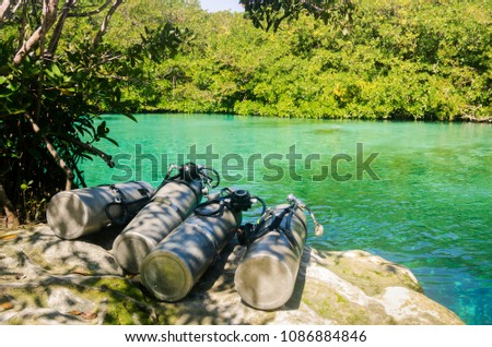 bunch of diving tanks and green crystal water #1086884846