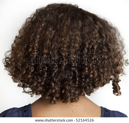 Bunch of dreadlocks of dark brown frizzy hair, on the back of the head of a young girl