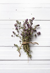Bunch of dried thyme on a white wooden background, rustic style, top view