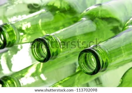 Bunch of empty glass beer bottles with back lighting.