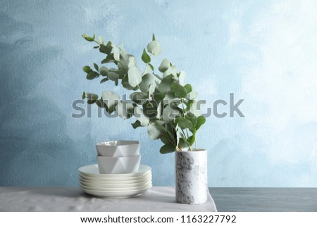 Bunch of eucalyptus branches with fresh leaves in vase and dishware on table
