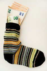 Bunch of Euro's. Close-up. Saving money in sock. Euro banknotes out from it. Keeping savings at home. Finance, savings, investing. Money management at home. Financial business concept.