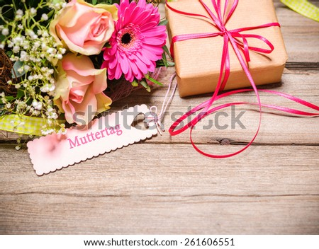 Bunch of flowers and tag with german text on wooden background.Mothers Day