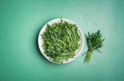 Bunch of fresh arugula in a white plate and an arugula bundle near it on a green mint table. Above view of harvested arugula. Making arugula salad.