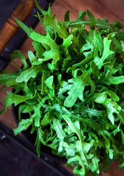 Bunch of fresh arugula leaves on a wooden tray. Top view.