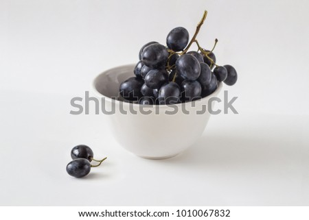 bunch of fresh black grapes in a white ceramic bowl on a light background