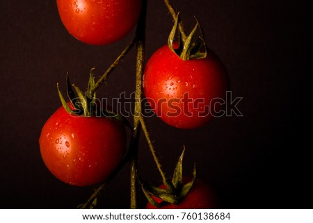 Shutterstock Bunch of fresh cherry tomatoes on a black background. Toned.