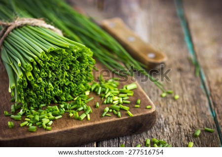 bunch of fresh chives on a wooden cutting board, selective focus Foto stock ©