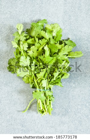 Bunch of fresh coriander on a blue worktop