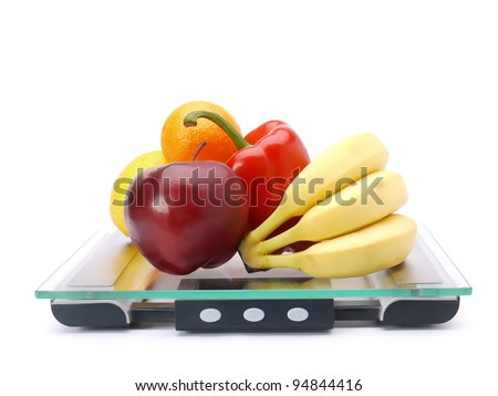 Bunch of fresh fruits and vegetables on glass bathroom scales shot on white