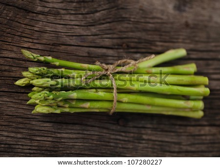 Bunch of fresh green asparagus spears tied with string on a rustic wooden table
