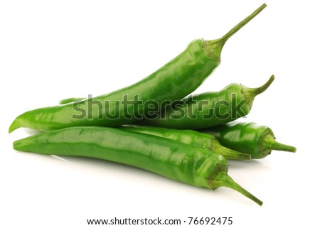 bunch of fresh  green chili peppers on a white background