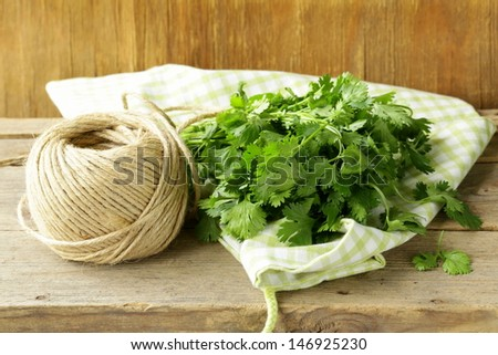 bunch of fresh green coriander (cilantro) on a wooden table