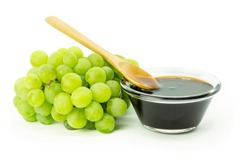 Bunch of fresh green grape and grape molasses in glass bowl isolated on white background, clipping path. Food sauce concept