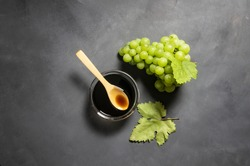 Bunch of fresh green grape and grape molasses in glass bowl on rustic background, clipping path. Food sauce concept