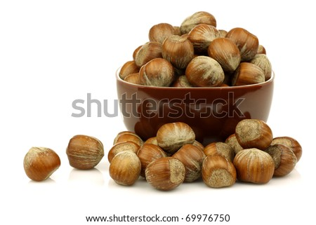 bunch of fresh hazelnuts in a brown bowl on a white background