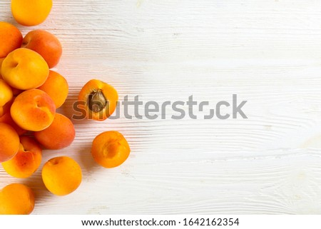 Bunch of fresh organic apricot fruits laid out on textured background. Clean eating concept. Healthy nutritious vegan snack, tasty raw diet. Close up, copy space, top view, flat lay.