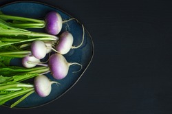 bunch of fresh radish in a blue plate on black background with space for the text on the right. top view
