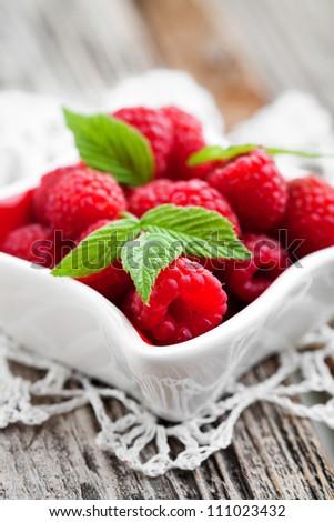 Bunch of fresh raspberries in white bowl