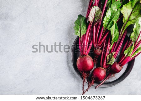 Photo of  Bunch of fresh raw organic beets with leaves on a gray stone background