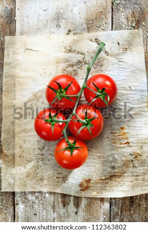 Bunch of fresh red tomatoes in grungy kitchen on a piece of stained, wrinkled oily oven paper on an old wooden tabletop