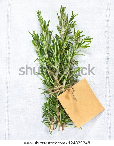 Bunch of fresh rosemary with tag on a white linen napkin.