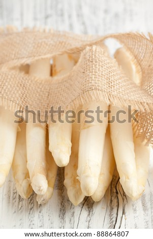 Bunch of fresh white asparagus on white wooden table - stock photo