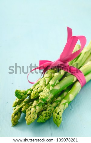 Bunch of fresh young asparagus tips tied with a decorative pink ribbon - stock photo