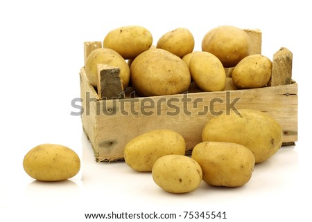 bunch of freshly harvested potatoes in a wooden box and some beside it on a white background