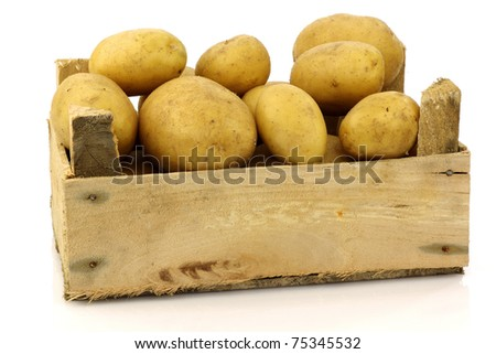 bunch of freshly harvested potatoes in a wooden box on a white background