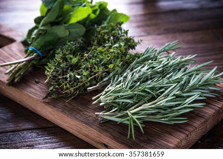 bunch of garden fresh herbs on wooden board from above - Shutterstock ID 357381659