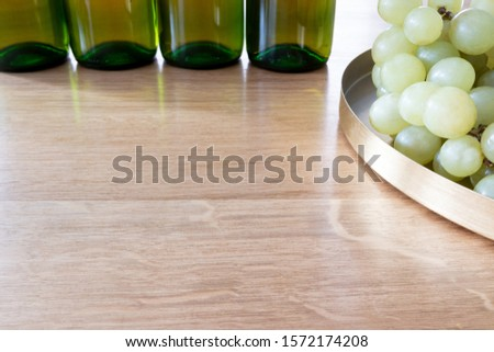 Photo of Bunch of grapes and a bottle of organic wine on a wooden table as a background. Front perspective view. Copy space in front of the picture.