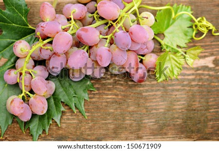 Bunch of grapes on old wooden table #150671909