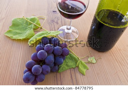 Bunch of grapes with a glass of wine and bottle